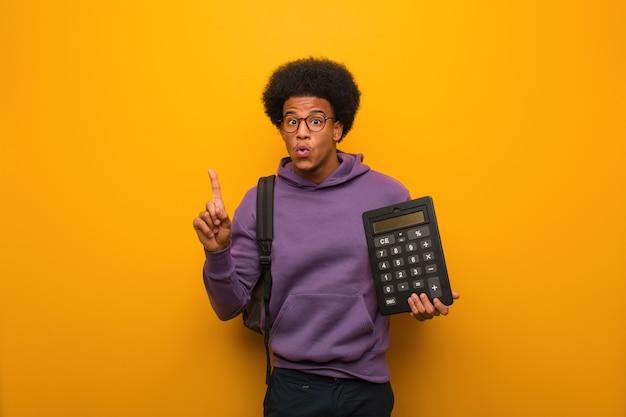 Homem jovem estudante afro-americano, segurando uma calculadora, tendo uma ótima idéia