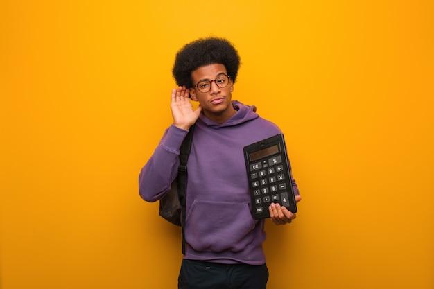 Homem jovem estudante afro-americano, segurando uma calculadora tentar ouvir uma fofoca