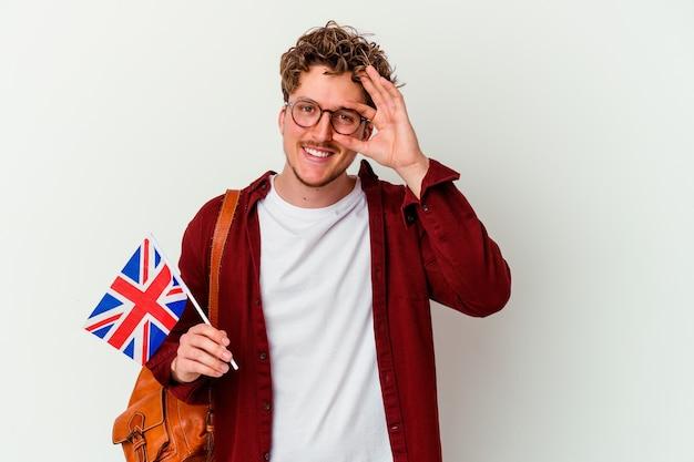 Homem jovem estudante aprendendo inglês isolado na parede branca animado, mantendo o gesto de aprovação no olho.