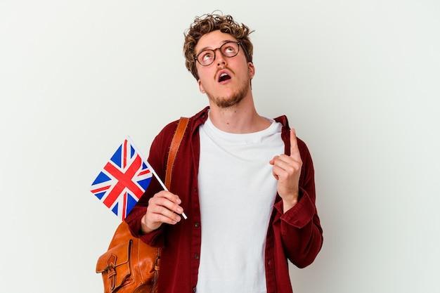 Homem jovem estudante aprendendo inglês isolado na parede branca, apontando para cima com a boca aberta.