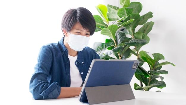 Homem jovem estudante asiático usando máscara de proteção, trabalhando com um computador laptop enquanto estuda online