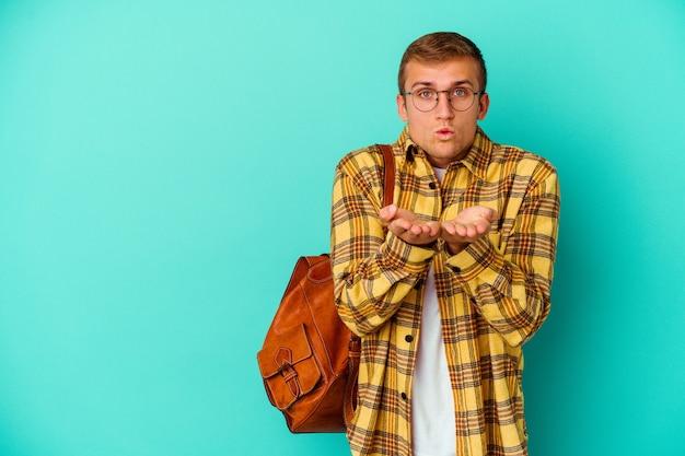 Homem jovem estudante caucasiano isolado em azul dobrando os lábios e segurando as palmas das mãos para enviar beijo no ar.