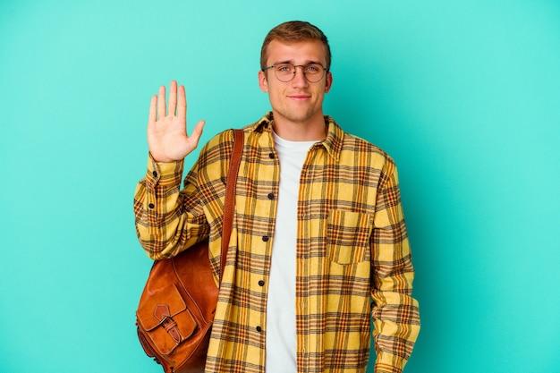 Homem jovem estudante caucasiano isolado em azul sorrindo alegre mostrando o número cinco com os dedos.