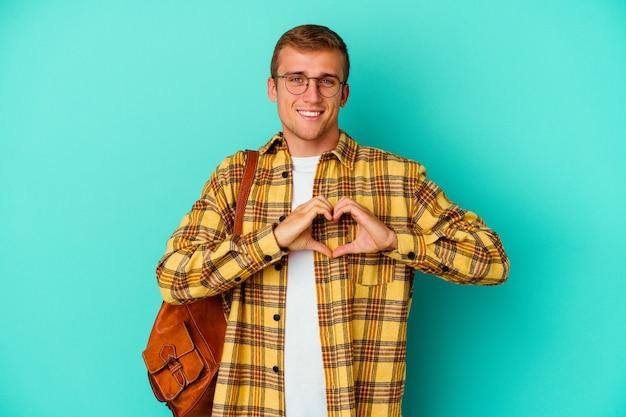 Homem jovem estudante caucasiano isolado em azul sorrindo e mostrando uma forma de coração com as mãos.