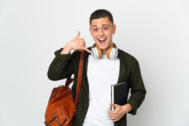 Homem jovem estudante caucasiano isolado no fundo branco, fazendo gesto de telefone. ligue-me de volta sinal