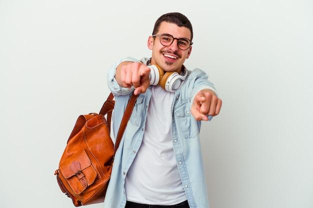 Homem jovem estudante caucasiano ouvindo música isolada em sorrisos alegres de fundo branco, apontando para a frente.