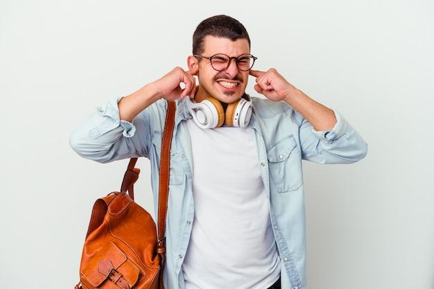 Homem jovem estudante caucasiano ouvindo música isolada no fundo branco, cobrindo as orelhas com as mãos.
