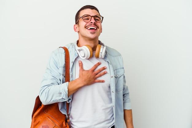 Homem jovem estudante caucasiano ouvindo música isolada no fundo branco ri alto, mantendo a mão no peito.