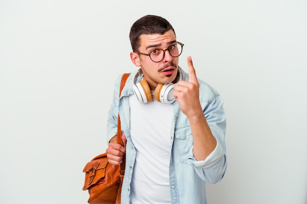 Homem jovem estudante caucasiano ouvindo música isolada no fundo branco, tendo uma ideia, o conceito de inspiração.