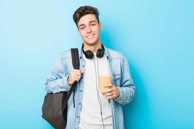 Homem jovem estudante caucasiano segurando um café para viagem feliz, sorridente e alegre.