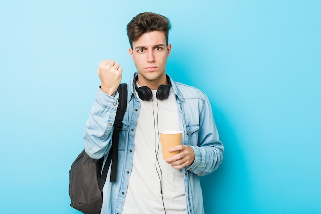 Homem jovem estudante caucasiano segurando um café para viagem, mostrando o punho para expressão facial agressiva.
