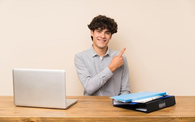 Homem jovem estudante com um laptop apontando para o lado para apresentar um produto
