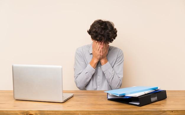 Homem jovem estudante com um laptop com expressão cansado e doente