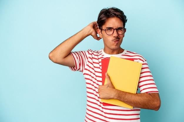 Homem jovem estudante de raça mista segurando livros isolados em um fundo azul tocando a parte de trás da cabeça, pensando e fazendo uma escolha.