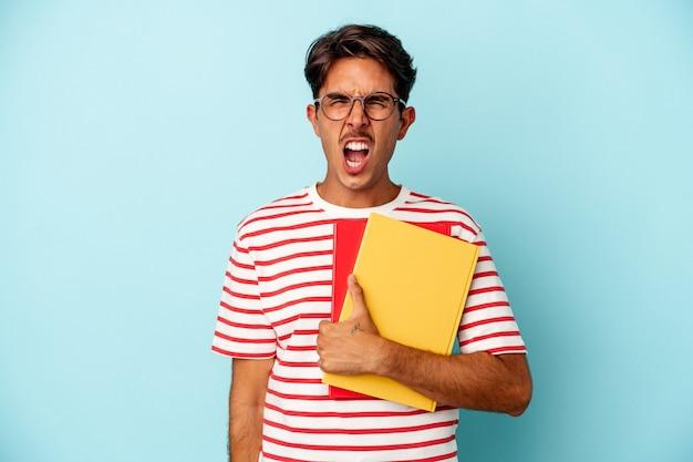 Homem jovem estudante de raça mista segurando livros isolados sobre fundo azul, gritando muito zangado e agressivo.