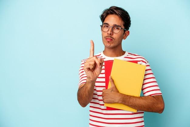 Homem jovem estudante de raça mista segurando livros isolados sobre fundo azul, mostrando o número um com o dedo.