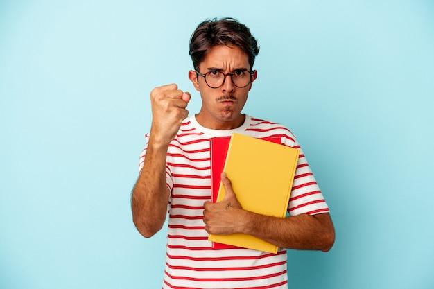 Homem jovem estudante de raça mista segurando livros isolados sobre fundo azul, mostrando o punho para a câmera, expressão facial agressiva.