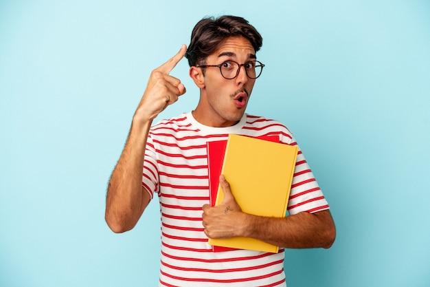 Homem jovem estudante de raça mista segurando livros isolados sobre fundo azul, tendo uma ideia, o conceito de inspiração.