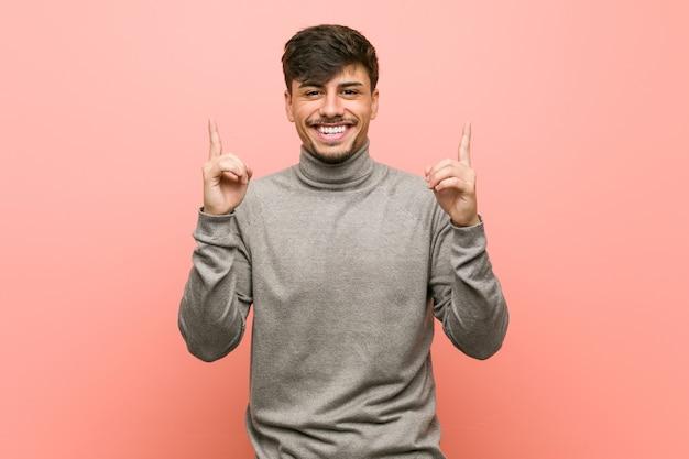 Homem jovem estudante inteligente indica com os dois dedos indicadores mostrando um espaço em branco.