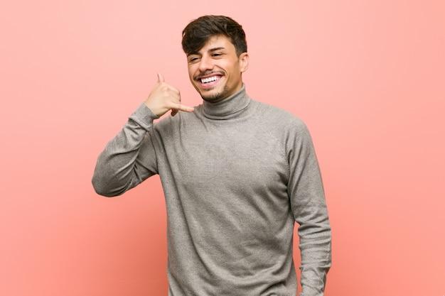 Homem jovem estudante inteligente, mostrando um gesto de chamada de telefone móvel com os dedos.
