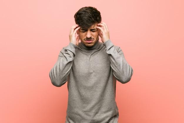 Homem jovem estudante inteligente tocando os templos e tendo dor de cabeça.
