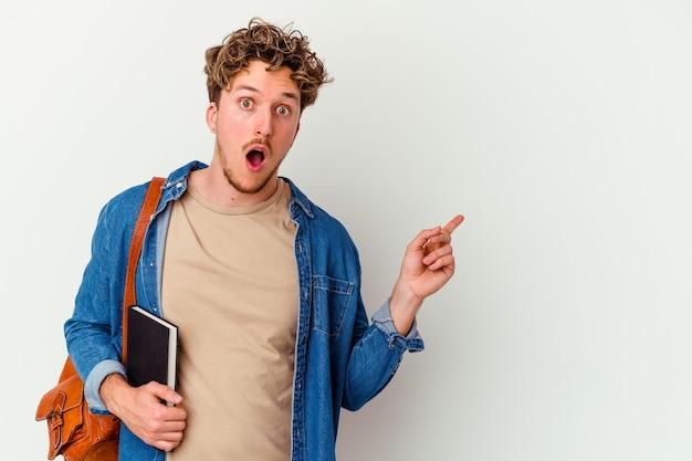 Homem jovem estudante isolado na parede branca apontando para o lado