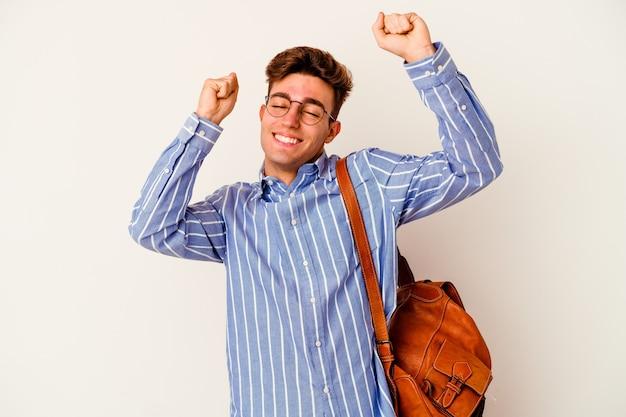 Homem jovem estudante isolado na parede branca comemorando um dia especial, pula e levanta os braços com energia.