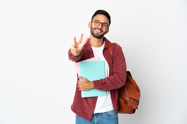 Homem jovem estudante isolado na parede branca feliz e contando três com os dedos