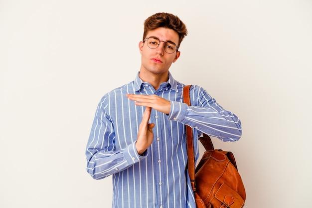 Homem jovem estudante isolado na parede branca mostrando um gesto de tempo limite