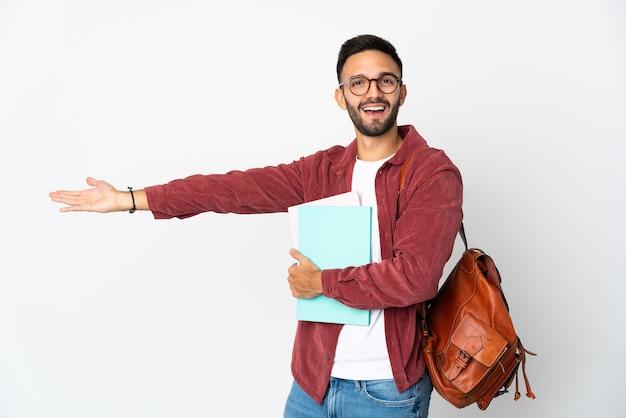 Homem jovem estudante isolado no fundo branco, estendendo as mãos para o lado para convidar para vir