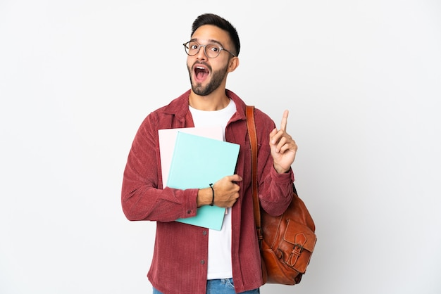 Homem jovem estudante isolado no fundo branco pensando em uma ideia apontando o dedo para cima