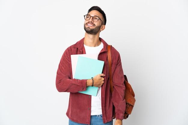 Homem jovem estudante isolado no fundo branco pensando em uma ideia enquanto olha para cima