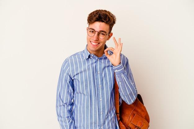 Homem jovem estudante isolado no fundo branco pisca um olho e segura um gesto de ok com a mão.