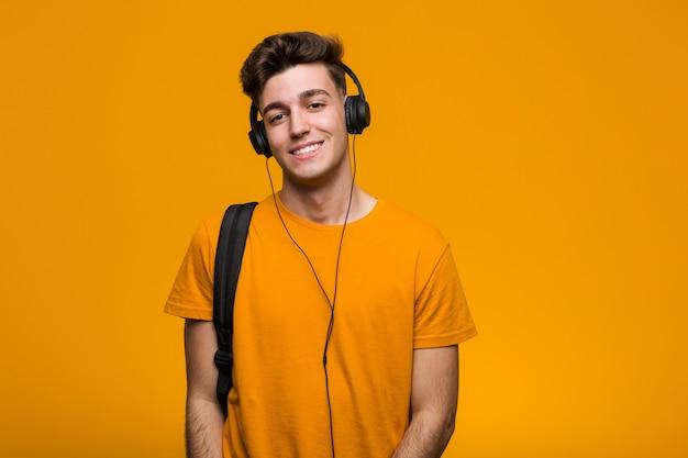 Homem jovem estudante legal ouvir música com fones de ouvido, sorrindo e levantando o polegar