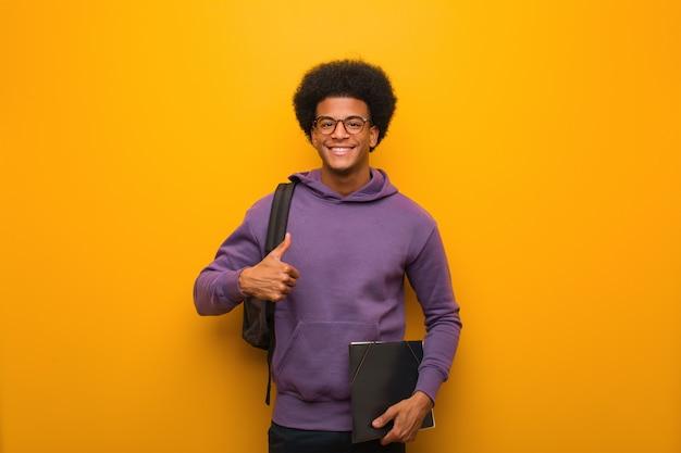 Homem jovem estudante negro sorrindo e levantando o polegar