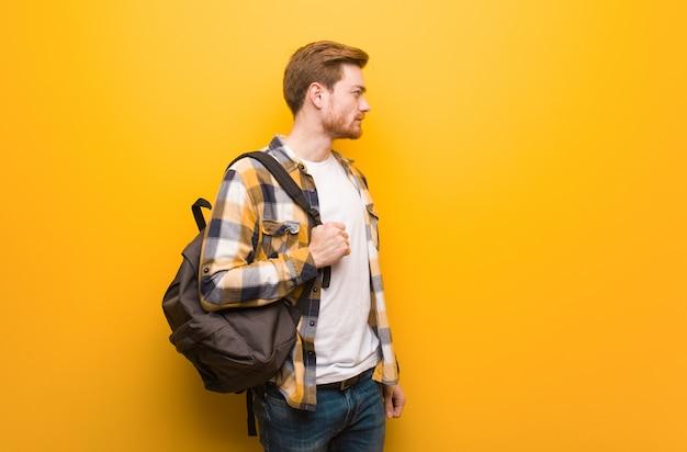 Homem jovem estudante ruiva do lado olhando para a frente
