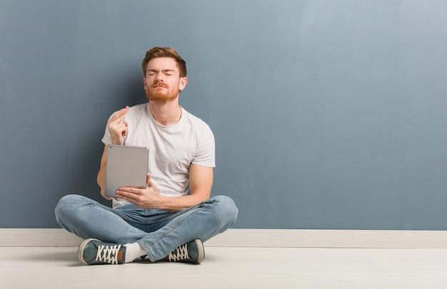 Homem jovem estudante ruiva sentada no chão cruzando os dedos por ter sorte. ele é