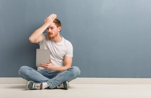 Homem jovem estudante ruiva sentada no chão, preocupado e oprimido. ele está segurando um tablet.