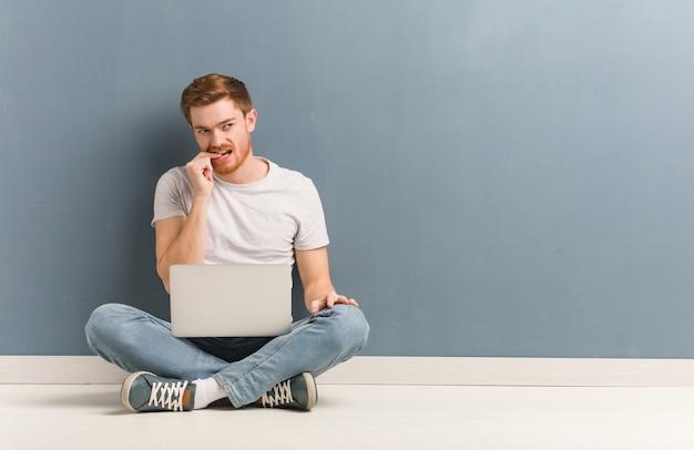 Homem jovem estudante ruiva sentada no chão relaxado pensando em alguma coisa
