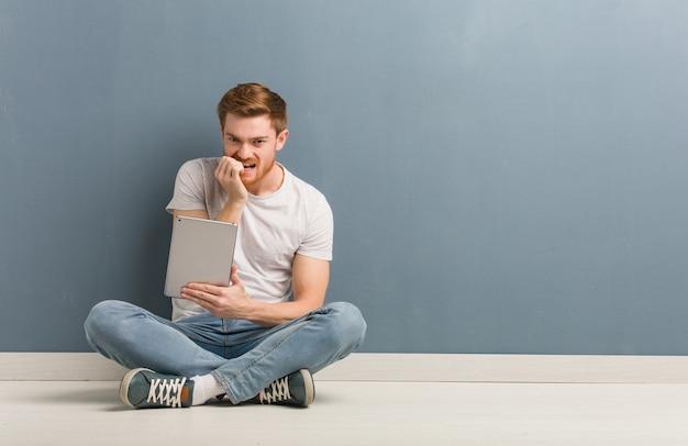 Homem jovem estudante ruiva sentada no chão roer unhas, nervoso e muito ansioso. ele está segurando um tablet.