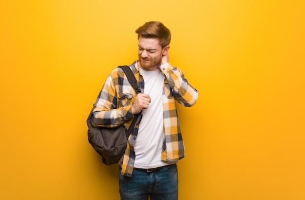 Homem jovem estudante ruiva sofrendo dor no pescoço