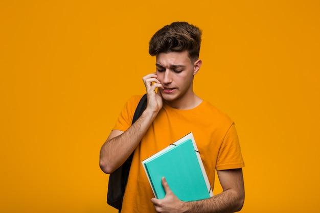 Homem jovem estudante segurando livros cruzando os dedos por ter sorte