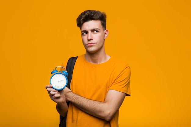Homem jovem estudante segurando um despertador, roendo as unhas, nervoso e muito ansioso.