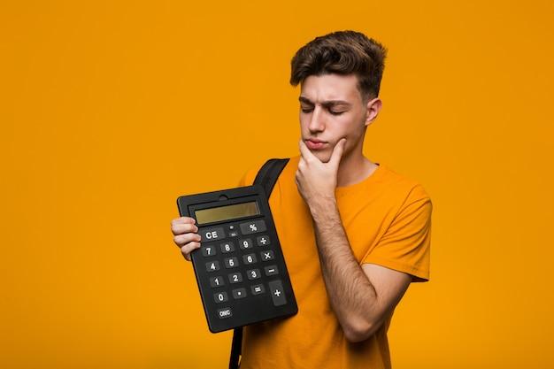 Homem jovem estudante segurando uma calculadora de pé com a mão estendida, mostrando o sinal de stop, impedindo-o.