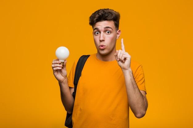 Homem jovem estudante segurando uma lâmpada relaxado pensando em algo olhando para um espaço de cópia.