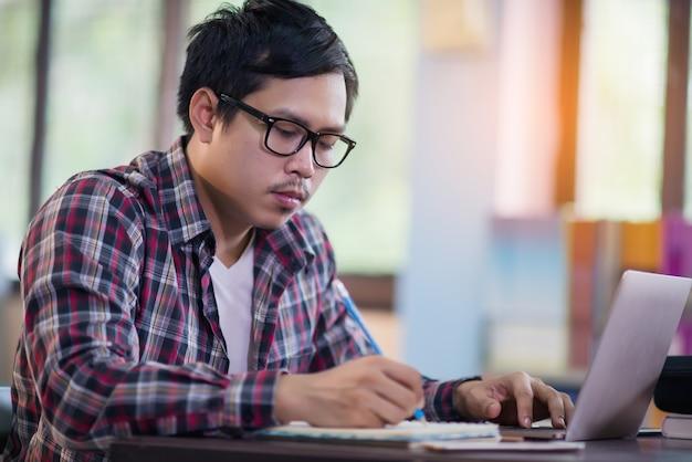 Homem jovem estudante sentado à mesa e tomar notas no caderno