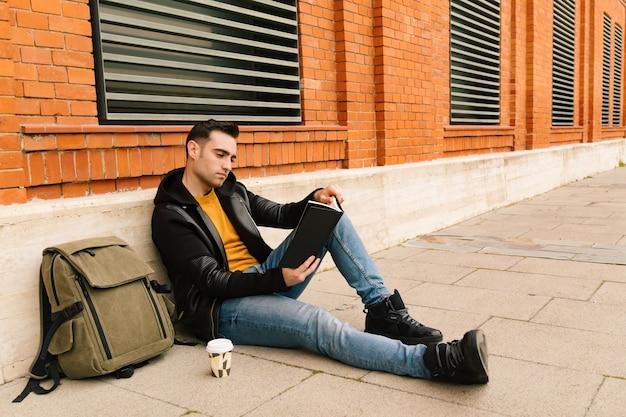 Homem jovem estudante sentado em uma rua da cidade, lendo um livro ao ar livre com um café. conceito de leitura e estilo de vida.