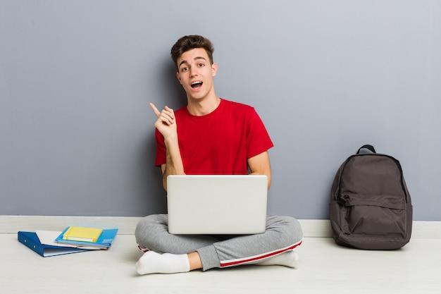 Homem jovem estudante sentado no chão de sua casa segurando um laptop