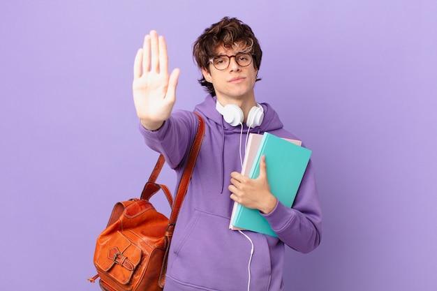 Homem jovem estudante sério mostrando a palma da mão aberta fazendo gesto de pare