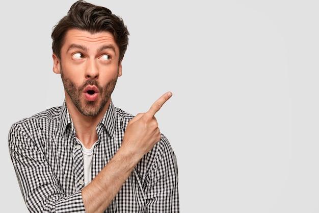Homem jovem europeu estupefato e surpreso com expressão de choque, veste camisa xadrez casual, aponta com o dedo indicador no canto superior direito, tem cerdas escuras, isolado sobre parede branca